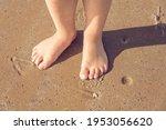 Child's Feet On Sandy Beach....