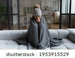 Small photo of Frozen. Sad latina female sit on couch at freezing cooled studio flat in warm cap and blanket shiver tremble with cold. Unhappy young lady spend time at home feel bad suffer of heating system problems