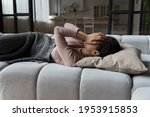 Small photo of Insomnia. Drowsy latin woman lie on sofa on back hide face in palms feel weak fatigue has strong headache migraine attack. Depressed young lady spend sleepless night think of loneliness love problem