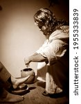 Small photo of Jesus Christ washing the feet of his apostles in a sign of service and humility. Sepia tones.