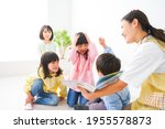 Small photo of Nursery teacher and children reading a picture book
