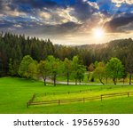 autumn landscape. fence near the meadow path on the hillside. forest in fog on the mountain at sunset - stock photo