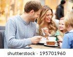 Family Enjoying Snack In Cafe...