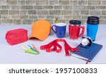 Small photo of Composition of different promo products with rich colors -Thermo mugs, Lanyards Neck Strap, pens, mug, silver table office clock, zipped coin purse fabric, notebook,cap On desk grey and background gre