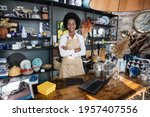 Small photo of Portrait of likable afro american woman in uniform and eyeglasses smiling and looking at camera. Modern shop with various decor on shelves.
