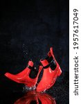 Small photo of Rubber rain shoes. Flying shoes. boots, galoshes. Levitation of shoes. Red women's shoes. Dark background.