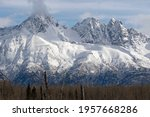 Twin Peaks, outside of Palmer, Alaska,  snow-covered on a mid-April day in 2021. The peak on left is East Twin Peak; to its right is West Twin Peak; and to the far right is the peak called Goat Rock.