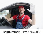Smiling courier driver in car cab waving his hand in greeting