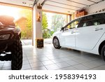Small photo of Home suburban countryside modern car and ATV double garage interior with wooden shelf, tools and equipment stuff storage warehouse indoors against sun light. Vehicle parked house parking background