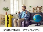 Small photo of Happy man traveler sitting on home sofa with packed luggage suitcase rejoice successful online ticket booking or hotel reservation holiday vacation with sale discount via laptop computer