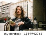 Small photo of Young pretty girl listening to music in the big city.She is seating at the table. girl in a leather jacket with headphones drinking coffee near business center . smiling and loathing.