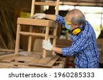 Small photo of Elder worker wood woodcraft retire hobby for good retirement, Asian male mature professional master of making wooden furniture with face mask protective.
