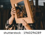 Small photo of The carpenters man high experienced wood worker making furniture. master of woodcraft male looking at workpiece closeup with fine detail.