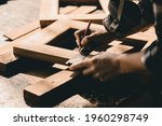 Small photo of The carpenters high experienced wood worker making furniture. master of woodcraft male work with wooden handcraft piece with fine detail.