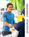Small photo of happy young man handing over credit card to a female cashier at till point