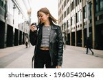 Small photo of Young pretty girl listening to music in the big city. girl in a leather jacket with headphones drinking coffee near business center . smiling and loathing