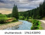 asphalt winding  road going along the river and passes through the green shaded forest in mountains - stock photo