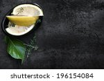 Lemon wedges with fresh thyme, in small black dish. - stock photo
