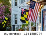 Historical Colonial Era Maryland Flag Calvert Arms Kings Colors featuring checkered yellow and black banner of Lord Baltimore and a Union Jack is hanging side by side with a US flag on a building