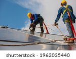 Small photo of Male two workers rope access height safety connecting with a knot safety clipping into roof fall arrest and fall restraint anchor point systems ready to ascending, construction site oil tank dome.
