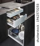 Small photo of Modern kitchen, Open drawers, Set of cutlery trays in kitchen drawer. Stainless steel drawer box side.Silk white matt drawer box side.