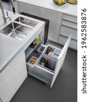 Small photo of Modern kitchen, Open pull out drawers, Sink waste bin in kitchen drawer. Stainless steel drawer box side.