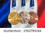 Small photo of April 25, 2021 Tokyo, Japan. Gold, silver and bronze medals of the XXXII Summer Olympic Games 2020 in Tokyo on the background of the flag of France.