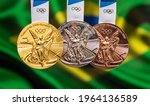 Small photo of April 25, 2021 Tokyo, Japan. Gold, silver and bronze medals of the XXXII Summer Olympic Games 2020 in Tokyo on the background of the flag of Brazil.