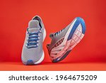 Small photo of Stability and cushion running shoes. New unbranded running sneaker or trainer on orange background. Men's sport footwear. Pair of sport shoes.