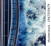 Small photo of Aerial view of people walking a gangway of a large cruise ship showing blue sea waves breaking at the side of the ship.