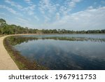A peaceful view of Lake Defuniak in Defuniak Springs, Florida, on a spring day with the sky reflecting in the water and a walkway.