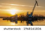 Small photo of Dredger is working to deepen the fairway on the river. Cleaning and deepening by a dredger on the river. Sunset on the river. Industrial concept.