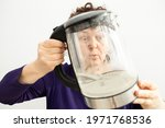Small photo of Woman looks through a transparent electric kettle with limescale. chalk residue of calcium carbonate. concept of repair of household appliances due to hard water.