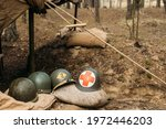 Metal Helmets Of United States Army Infantry Soldier At World War II. Helmets Near Camping Tent In Forest Camp.