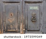 Small photo of Old damaged door, detail. One of the door knockers is missing. There is a sign written in Italian indicating the prohibition to introduce cycles and motorcycles.