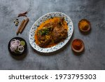 Small photo of Popular Indian mughul dish chicken chap prepared with big pieces of chicken meat in rich spicy gravy. A popular item of the mughul cuisine. Top view.