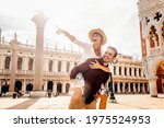 Small photo of Couple of tourists on vacation in Venice, Italy - Two lovers having fun on city street at sunset - Tourism and love concept
