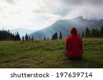 man meditating in the mountains at dawn - stock photo