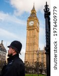 Small photo of London, UK - February 4, 2017: Juxtaposition with closeup of a guard and the Big Ben Clock tower in the background.