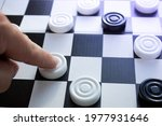 Small photo of Board game of checkers. Black and white chips for the game. Chess field. Checkers move close-up. Checker in hand.
