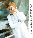 Small photo of Closeup portrait sad health care professional with headache, stressed, holding head against window glass. Nurse doctor with migraine overworked, overstressed isolated background hospital hall corridor
