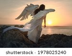 Small photo of an angel girl with big white wings stands on a mountain at dawn. Early morning, angel on the mountain. The white angel. Sunrise.