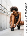 Small photo of Afro athlete woman tying her shoelaces.
