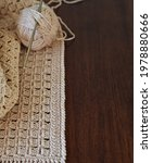 Small photo of Handmade crocheted with white cotton threads on a wooden table. A simple crochet pattern. Handmade crocheted with cotton threads on a wooden table. Handmade crocheted with cotton yarn.