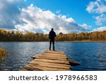 A Young Man Stands On A Wooden...