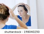 woman looking in a mirror. | Shutterstock . vector #198040250