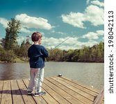 Young Boy Fishing From Dock On...