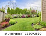Small photo of Fenced backyard. View of lawn and blooming flower beds