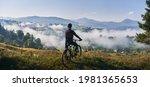 Man Riding Bicycle On Grassy...