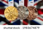 Small photo of April 25, 2021 Tokyo, Japan. Gold, silver and bronze medals of the XXXII Summer Olympic Games 2020 in Tokyo on the background of the flag of Great Britain.